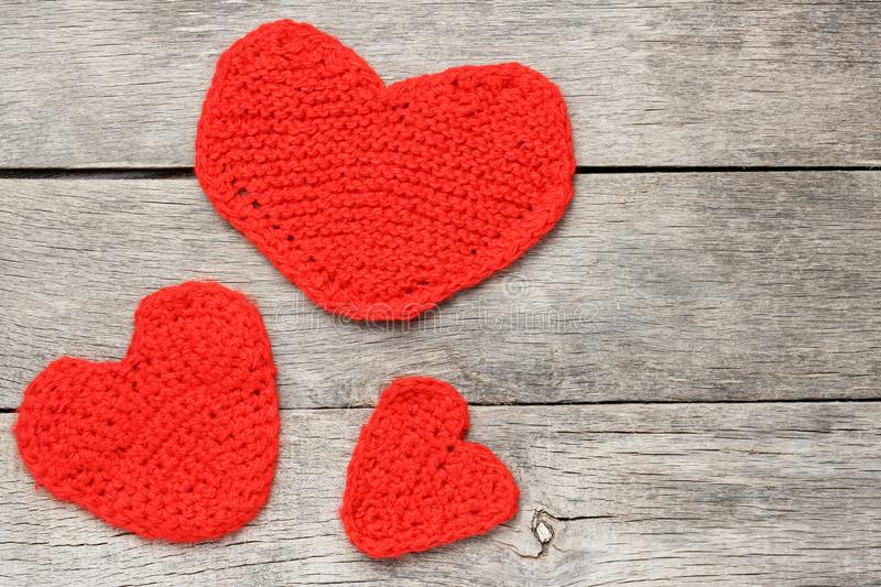 Three red knitted hearts on a gray wooden background, symbolizing love and family royalty free stock photography