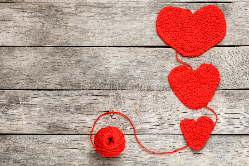 Three red knitted hearts on a gray wooden background, symbolizing love and family. Family relationship, bonds royalty free stock photography