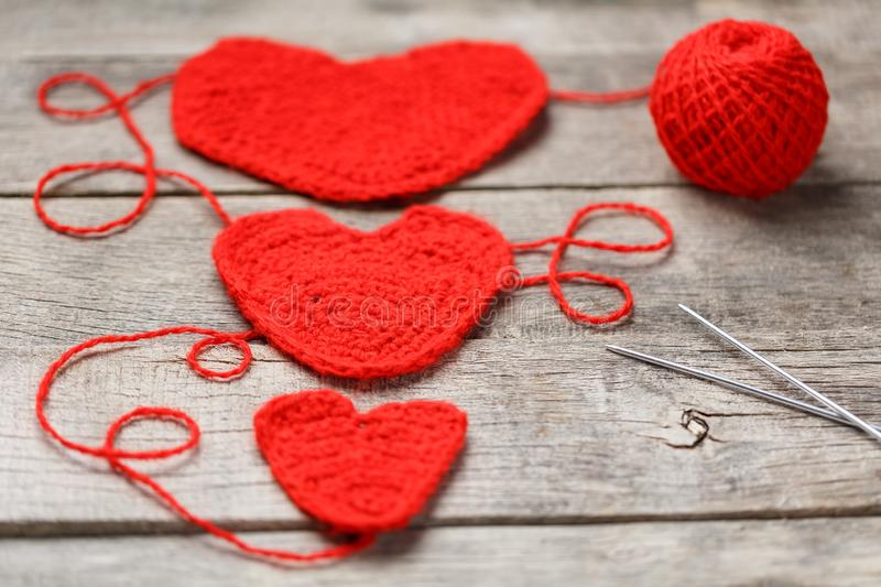 Three red knitted hearts on a gray wooden background, symbolizing love and family. Family relationship, bonds. Valentine`s Day. Knitting needles and a ball of royalty free stock photo