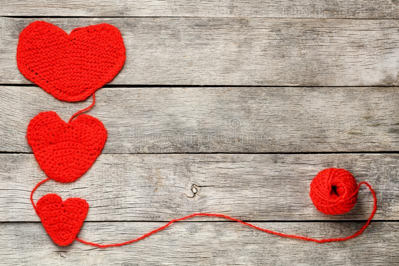 Three red knitted hearts on a gray wooden background, symbolizing love and family. Family relationship, bonds stock image