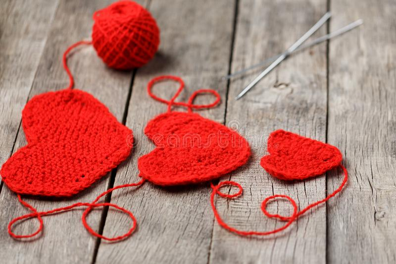 Three red knitted hearts on a gray wooden background, symbolizing love and family. Family relationship, bonds stock photography