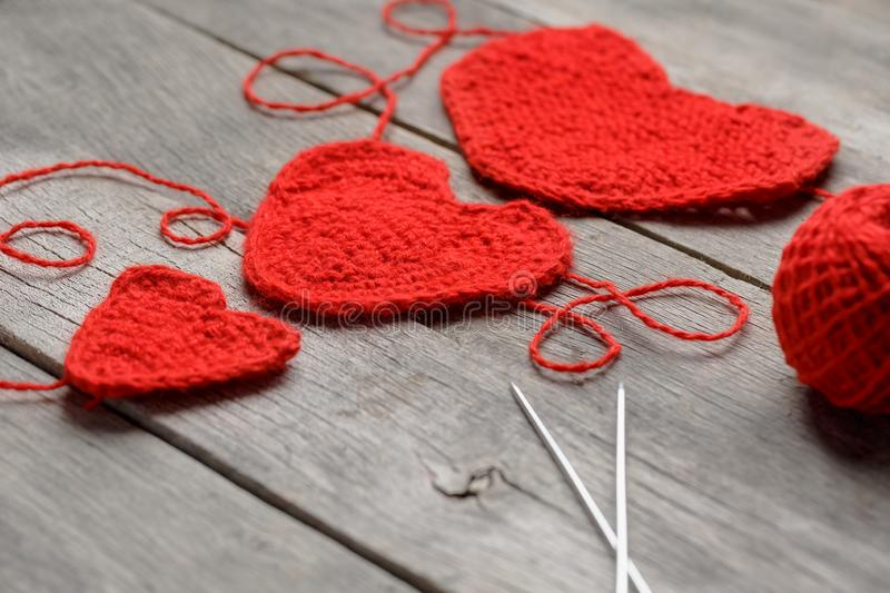 Three red knitted hearts on a gray wooden background, symbolizing love and family. Family relationship, bonds royalty free stock image