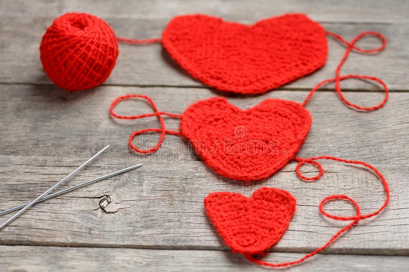 Three red knitted hearts on a gray wooden background, symbolizing love and family. Family relationship, bonds stock images