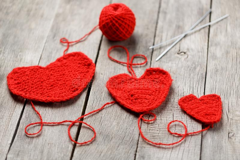Three red knitted hearts on a gray wooden background, symbolizing love and family. Family relationship, bonds royalty free stock photo