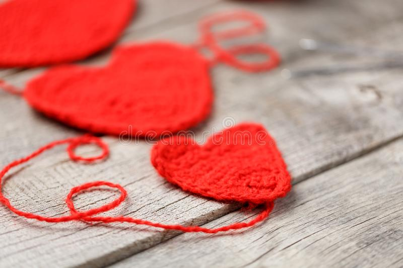 Three red knitted hearts on a gray wooden background, symbolizing love and family. Family relationship, bonds royalty free stock photos