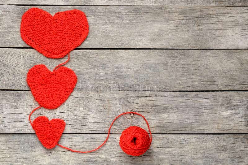 Three red knitted hearts on a gray wooden background, symbolizing love and family. Family relationship, bonds royalty free stock images