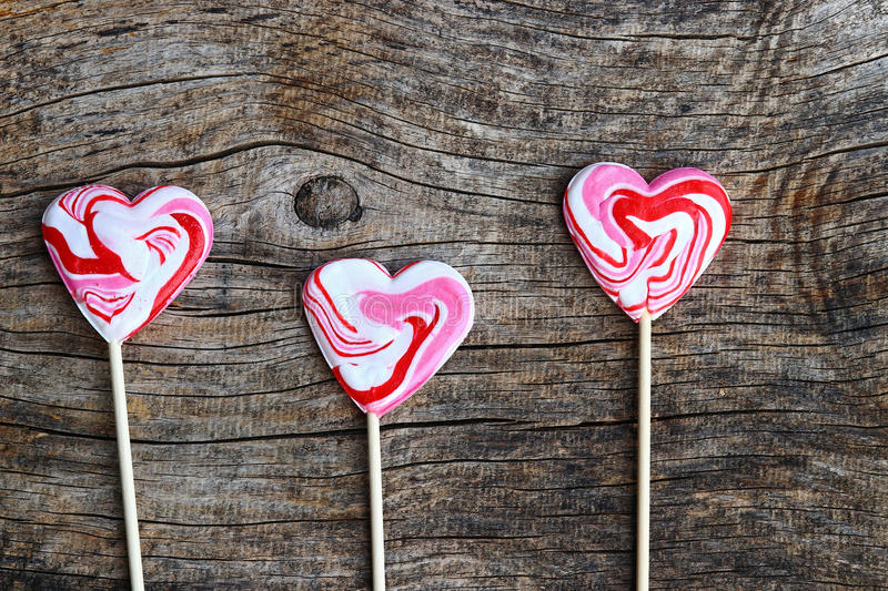 Three red lollipops in heart shape on wooden background stock photo