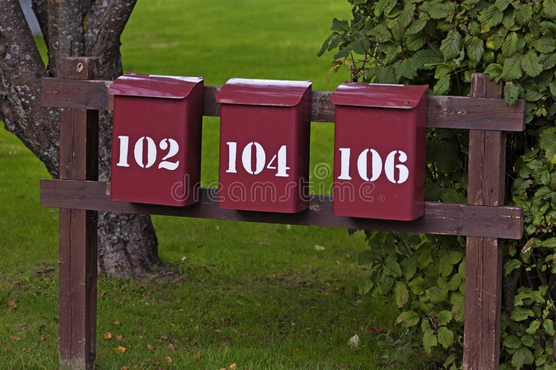 Three red mailboxes in a row with white text stock images