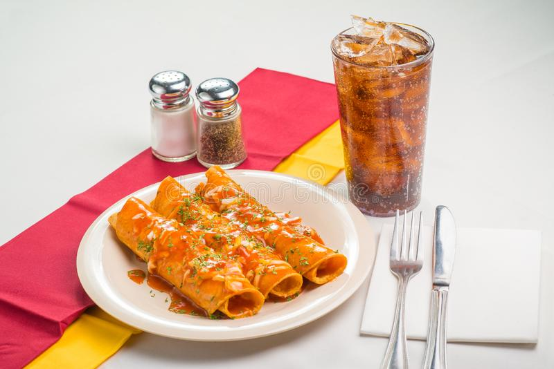 Three red Mexican Enchiladas with a Cola Drink stock photos