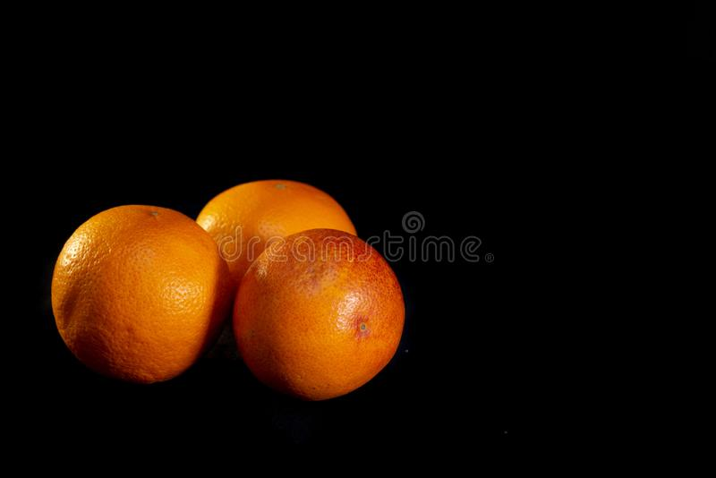 Three red oranges on a black background - image.  royalty free stock photos