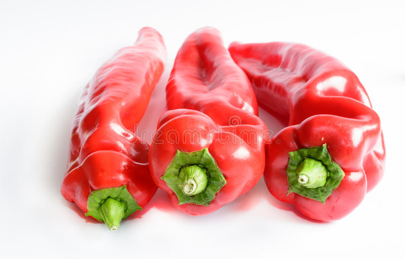 Three red peppers on white royalty free stock images