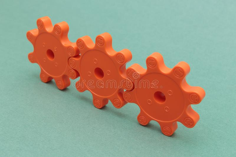 Three red plastic gears. On the green background royalty free stock images