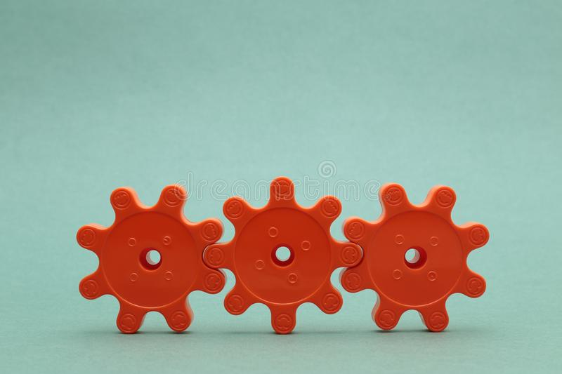 Three red plastic gears. On a green background stock image