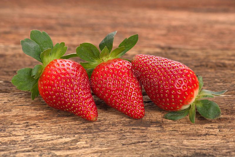 Three red ripe strawberries arranged on old rustic look timber stock image