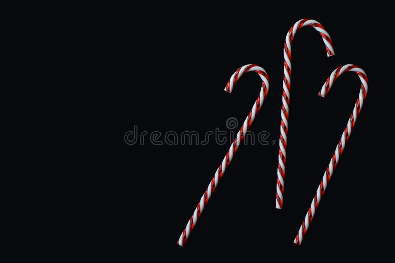 Three red and white striped traditional Christmas candy canes on black background stock photo