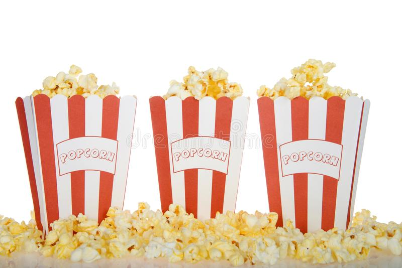 Three bags of buttered popcorn isolated on white background. Three red and white stripped bags labeled POPCORN filled with fresh butter popcorn with the same stock images