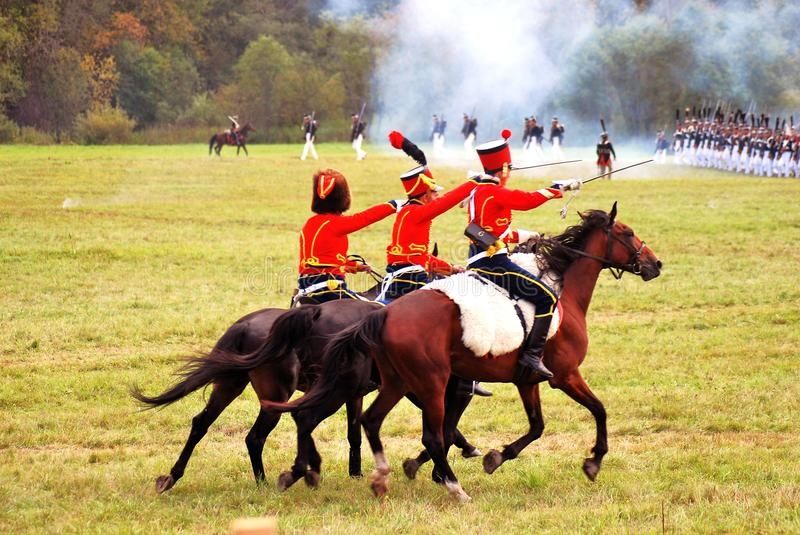 Three reenactors dressed as Napoleonic war soldiers ride horses royalty free stock photos