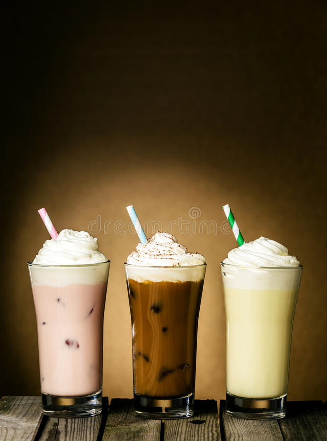 Three refreshing creamy milkshakes. In berry, chocolate and lemon flavors topped with a twirl of ice cream or frozen yoghurt on a wooden table against a brown stock photos