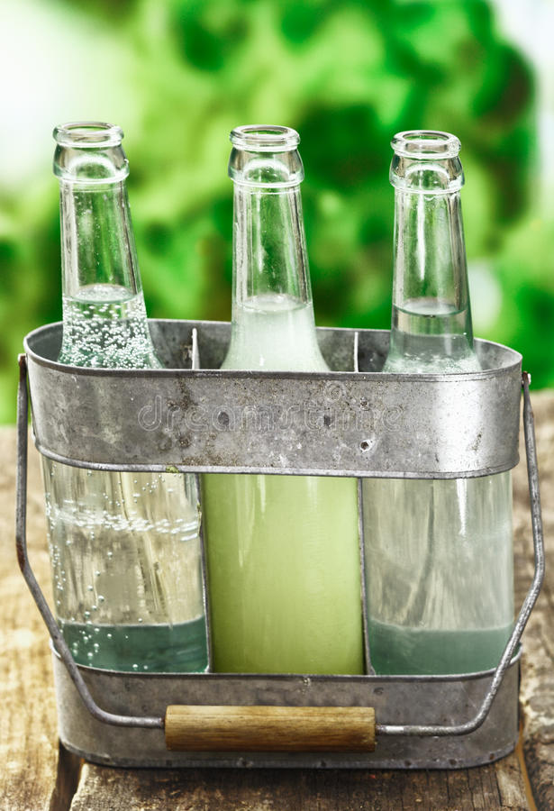 Three refreshing healthy drinks. Of pure fresh aerated and still water and fruit juice served in clear glass bottles in a rustic metal holder stock images