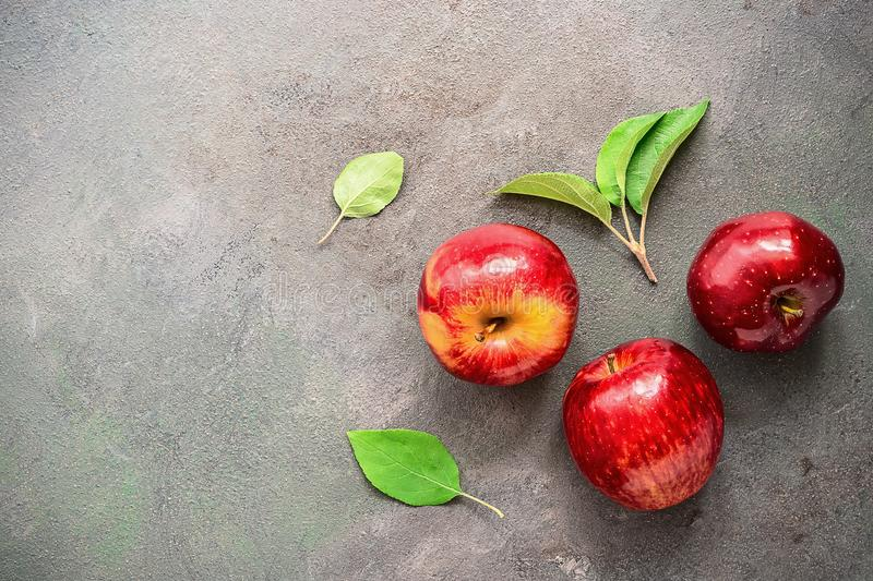 Three ripe bright red apples with green leaves on a rustic textured background, top view. Copy space stock photo
