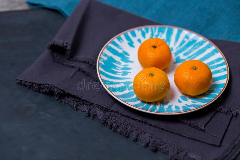 Three ripe delicious juicy Mandarin lie in a bright white with a blue plate patterns on fabric cloth kitchen towel on a dark blue royalty free stock images