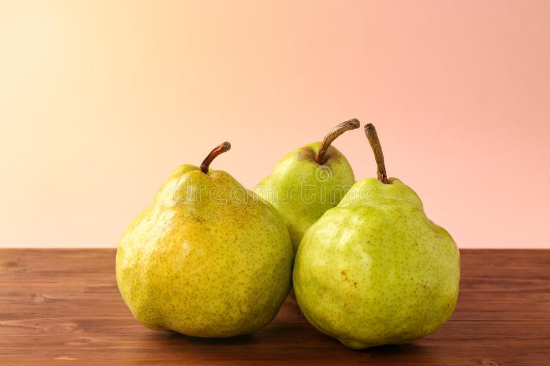 Three ripe, fresh, organic Green Anjou pears with the stems on a dark wooden table against bright pink background and sun light. Space for text royalty free stock images