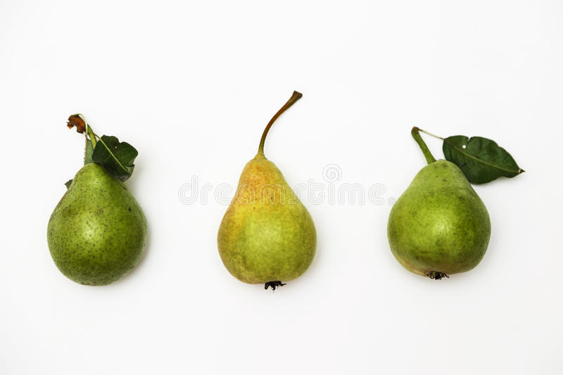 Three ripe green pears with a sprig lying in a row on a white background. Top view stock image