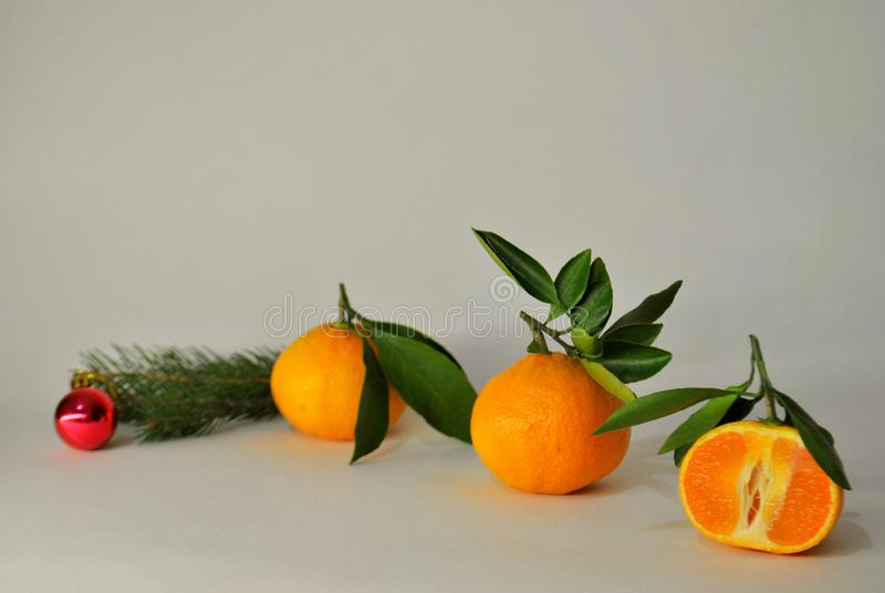 Three ripe juicy tangerines, a branch of spruce and Christmas tree toy on a white background. Three ripe juicy mandarins, a branch of spruce and Christmas tree royalty free stock photography