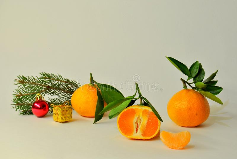 Three ripe juicy tangerines, a branch of spruce and a pair of Christmas tree decorations on a white background. Three ripe juicy mandarins, a branch of spruce stock images