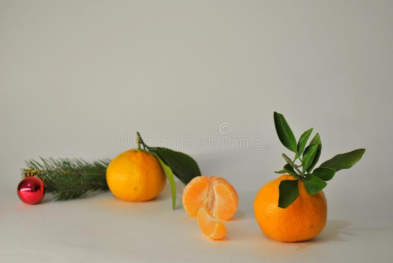 Three ripe juicy tangerines, a branch of spruce and Christmas tree toy on a white background. Three ripe juicy mandarins, a branch of spruce and a pair of royalty free stock photos