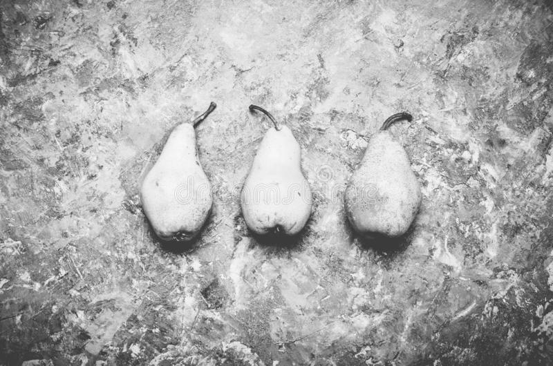 Three ripe pears on a rustic concrete table. Top view stock photography
