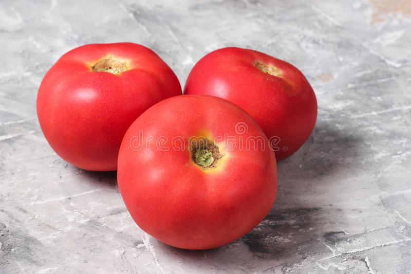 Three ripe tomatoes on a gray concrete background. stock images