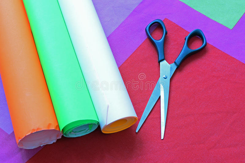 Three roll of papers and scissors. Scissors and three roll of papers ready for hobby crafts. Top view image royalty free stock photos