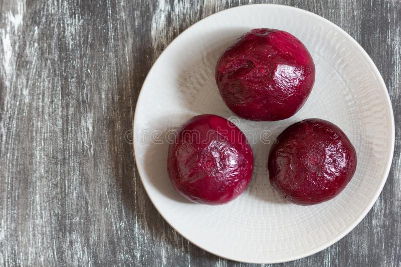 Three roots of cooked peeled beet on plate on the black background stock image
