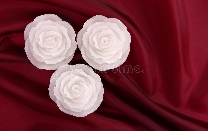 Download Three Rose Shaped Candles On Deep Red Satin Stock Photo - Image: 17682610