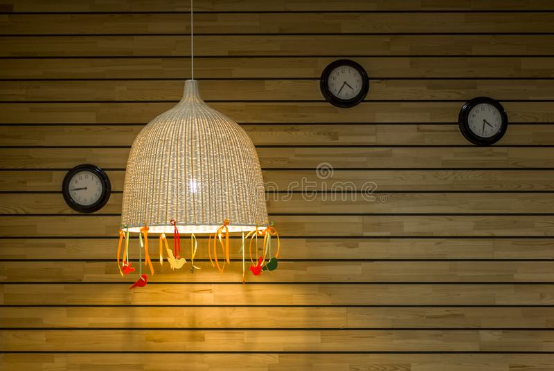 Three round black clocks on the wall of wooden light gray yellow boards with a large wicker lampshade. horizontal lines. natural stock photos