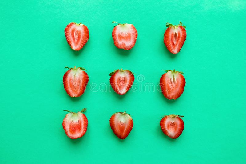Three rows from halves of red ripe strawberry on a bright turquoise background, top view. royalty free stock photo