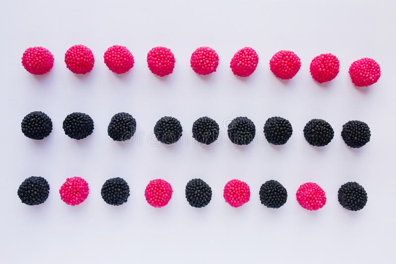 Three rows of jelly in the form of red raspberries and black blackberries on white background royalty free stock image