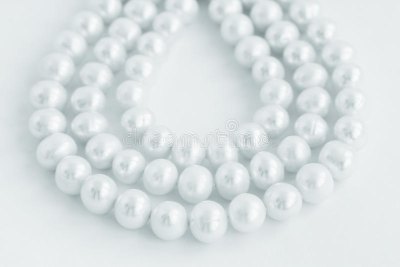 Three rows of natural pearl necklace on white royalty free stock photography