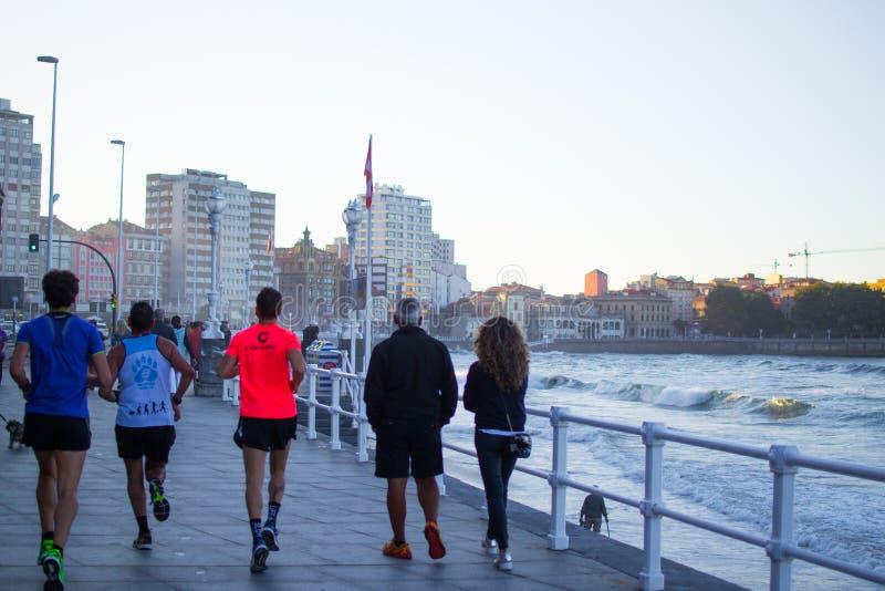 Three runners and pedestrians walking through Paseo de San Lorenzo, in Gijon, Asturias Spain stock photos