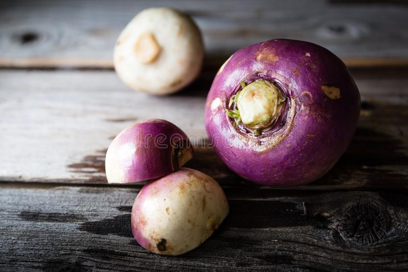 Three rutabaga lying on rustic wood background. royalty free stock images