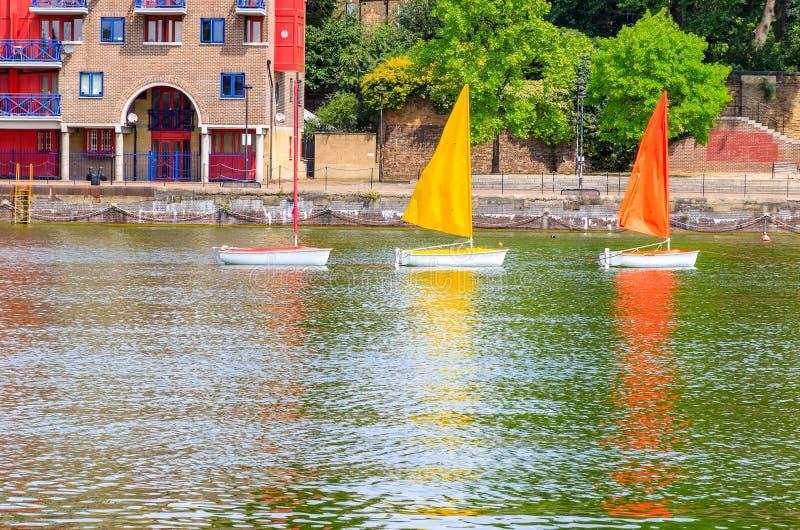 Three sailing dinghies float on Shadwell Basin in London. Three sailing dinghies in different colours float on Shadwell Basin in London stock photo
