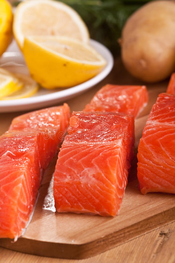 Three salmon pieces on a chopping board stock image