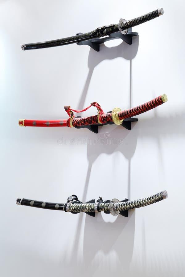Three Samurai Swords Hang On White Wall Stock Photos