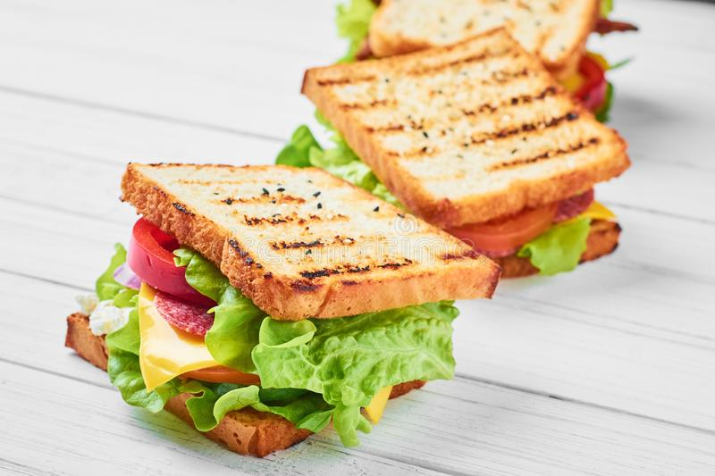 Three sandwiches with ham, lettuce and fresh vegetables on a white background stock images