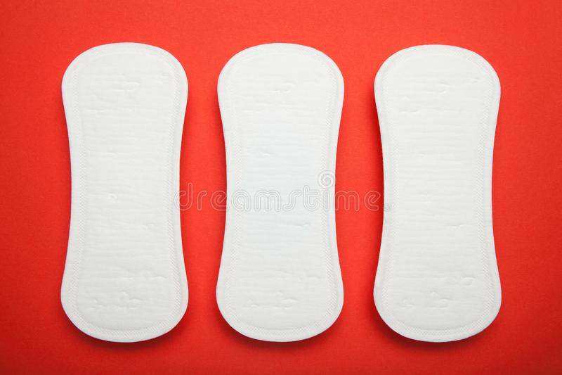 Three sanitary napkins on a red background.  royalty free stock photos