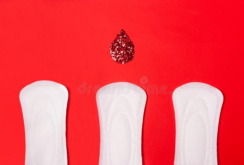 Three sanitary pads on a coral red women`s background stock image