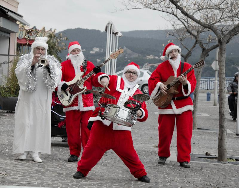 Three Santa Clauses Making Music. On the street. A scene from the French Riviera during the christmas holiday stock photography