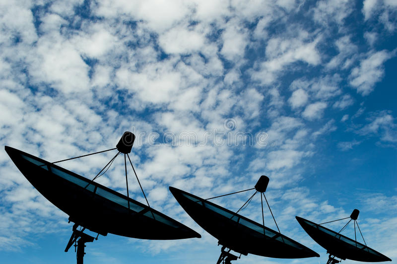 Three satellite dishes transmission data on background blue sky stock photography