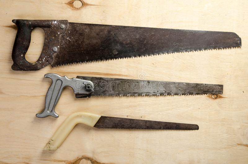 Three saws lying on a sheet of plywood. vintage. stock image